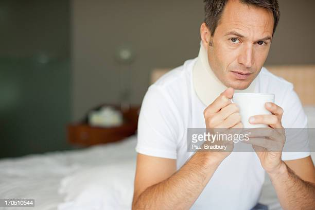Man sitting on bed with neck brace drinking coffee