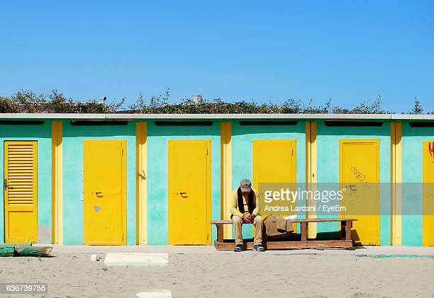 Man Sitting On Bench Against Beach Huts