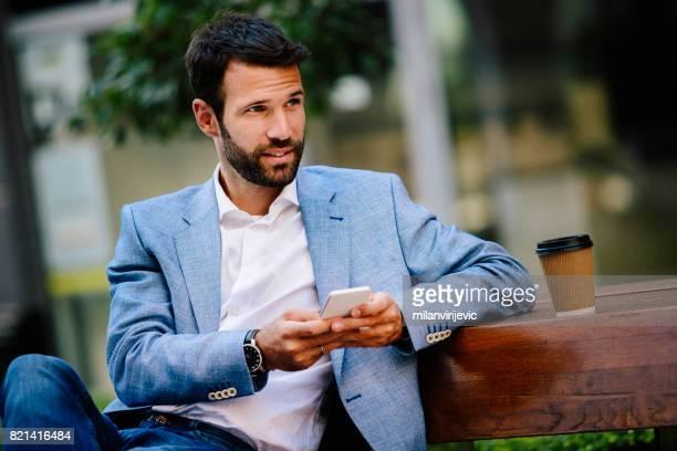 Mann auf der Bank sitzen und Nachricht eingeben