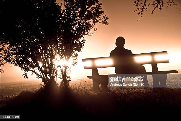 Man sitting on bench at night