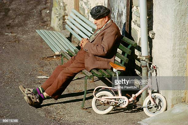 Man sitting on bench by bicycle