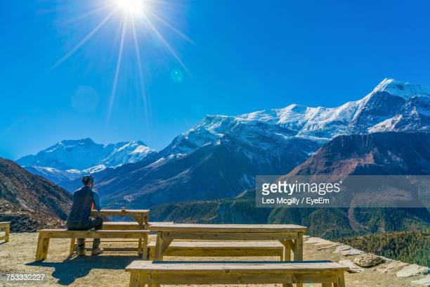 Man Sitting On Bench By Mountains