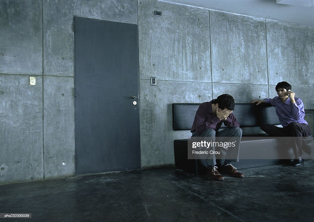 Man sitting on bench, head in hands, next to man on cell phone. : Stockfoto