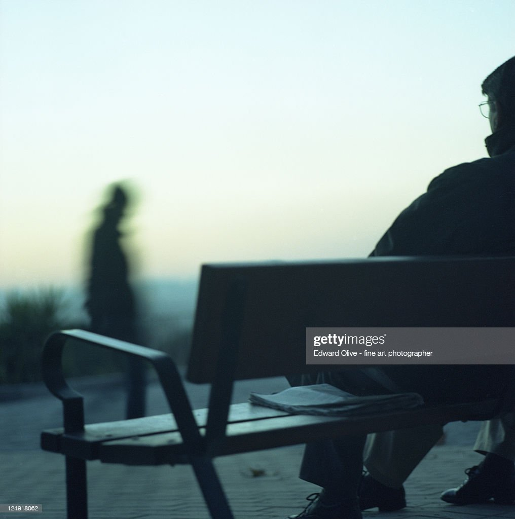 Man sitting on bench in cold evening light : Stock Photo