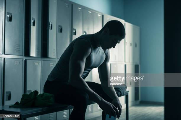 man sitting on bench in locker room after workout in gym - locker room stock pictures, royalty-free photos & images