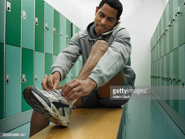 Man sitting on bench in locker room tying laces and using mobile phone