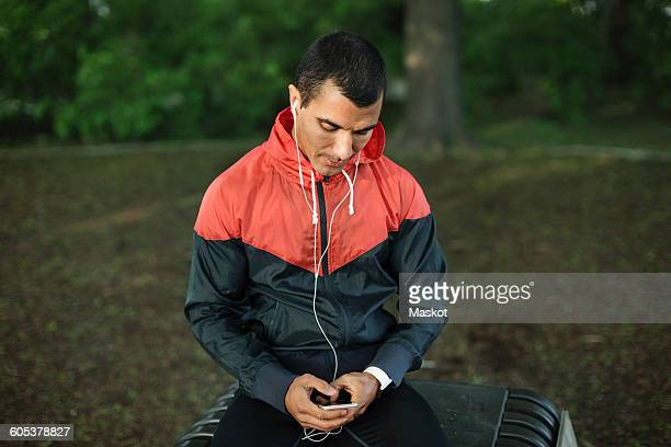 man sitting on bench listening music at park - sportsperson stock pictures, royalty-free photos & images