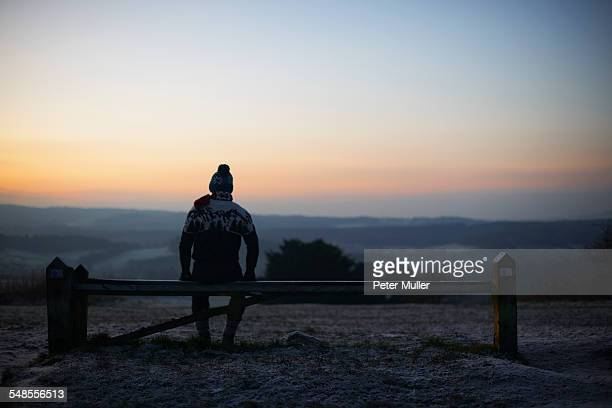 Man sitting on bench, looking at rural winter scene