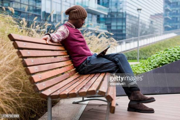 man sitting on bench looking at tablet - banco asiento fotografías e imágenes de stock