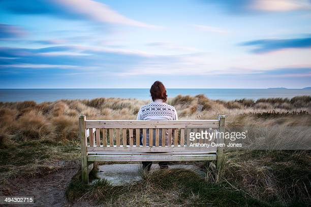 Man sitting on bench overlooking the sea