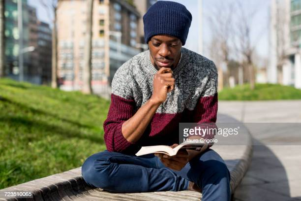 Man sitting on bench, reading book, thoughtful expression