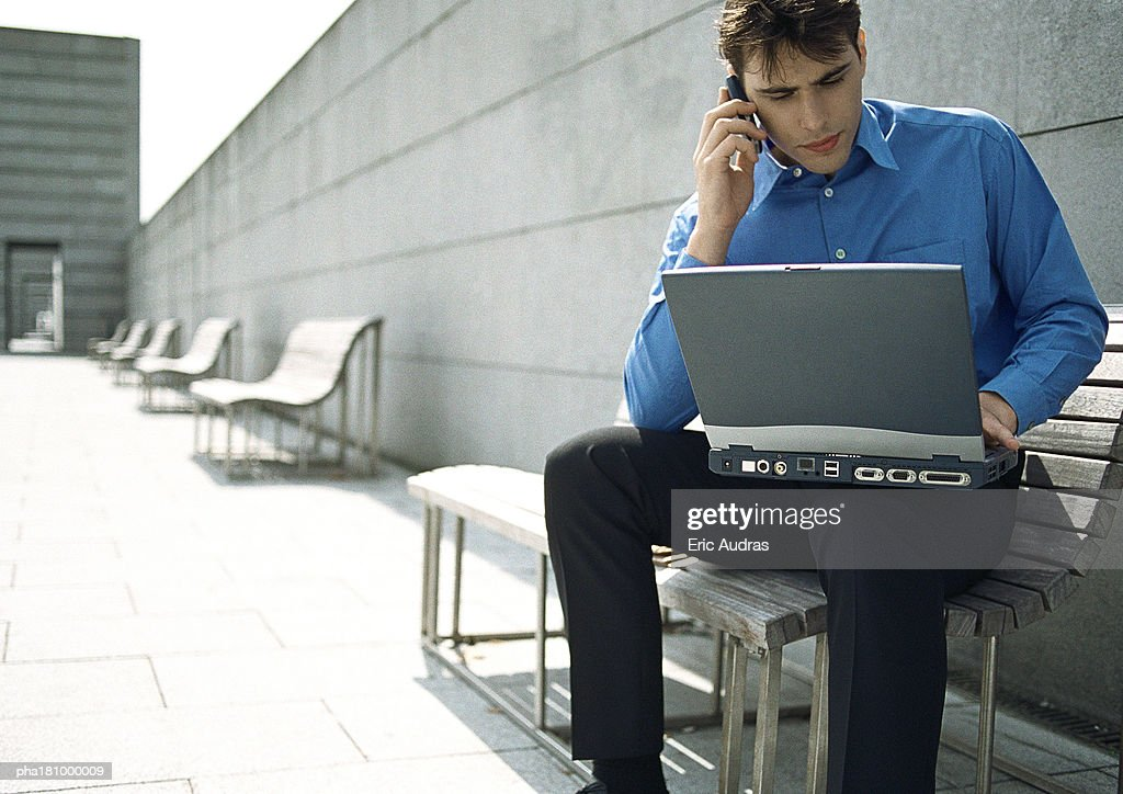 Man sitting on bench with cell phone and laptop : Stockfoto