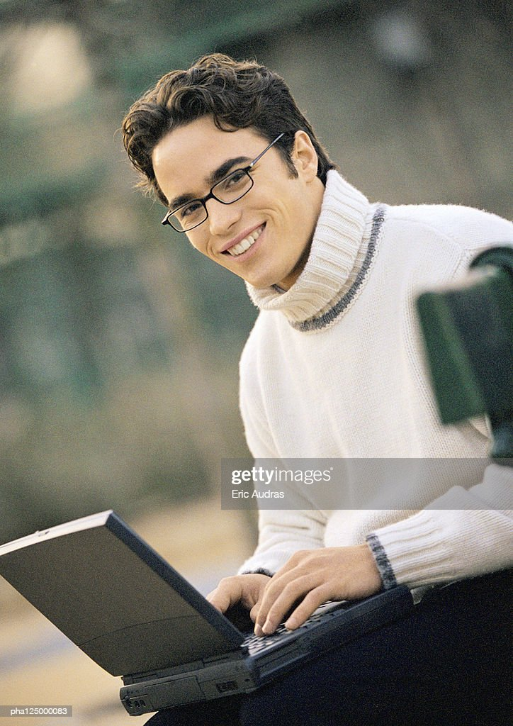 Man sitting on bench with laptop computer, portrait : Stockfoto