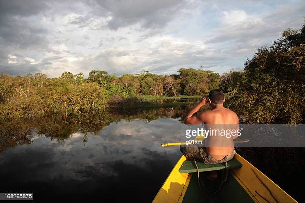 man sitting on boat in Amazon jungle river, Brazil