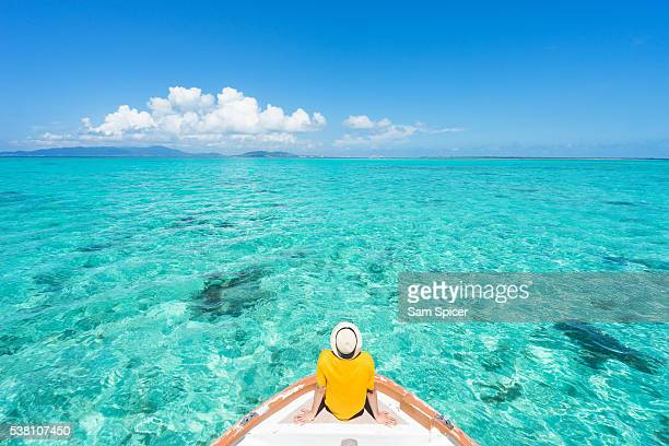 man sitting on boat sailing through tropical lagoon island paradise - okinawa prefecture stock pictures, royalty-free photos & images
