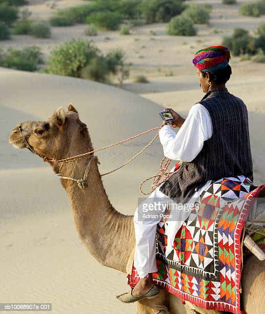 Man sitting on camel, using satellite navigation device