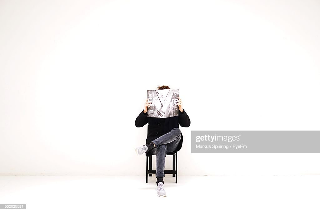 Man Sitting On Chair And Reading Magazine : Stock-Foto