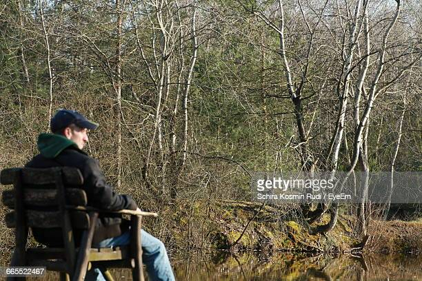 Man Sitting On Chair By Lake Against Bare Trees During Sunny Day