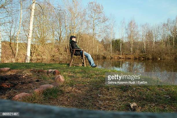 Man Sitting On Chair By Lake Against Trees During Sunny Day