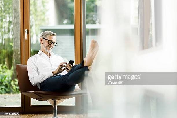 man sitting on chair in his living room text messaging - riqueza fotografías e imágenes de stock