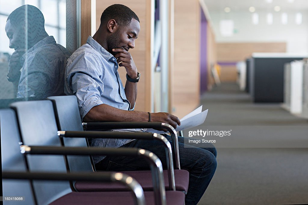 Man sitting on chair reading document : Stock Photo