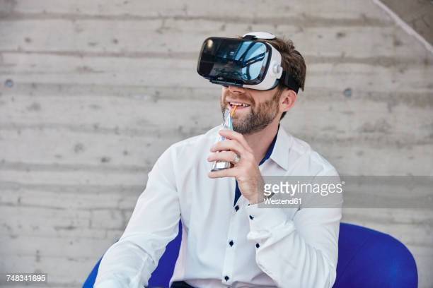 Man sitting on chair wearing VR glasses