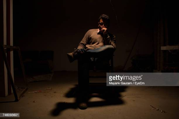 Man Sitting On Chair With Shadow In Darkroom