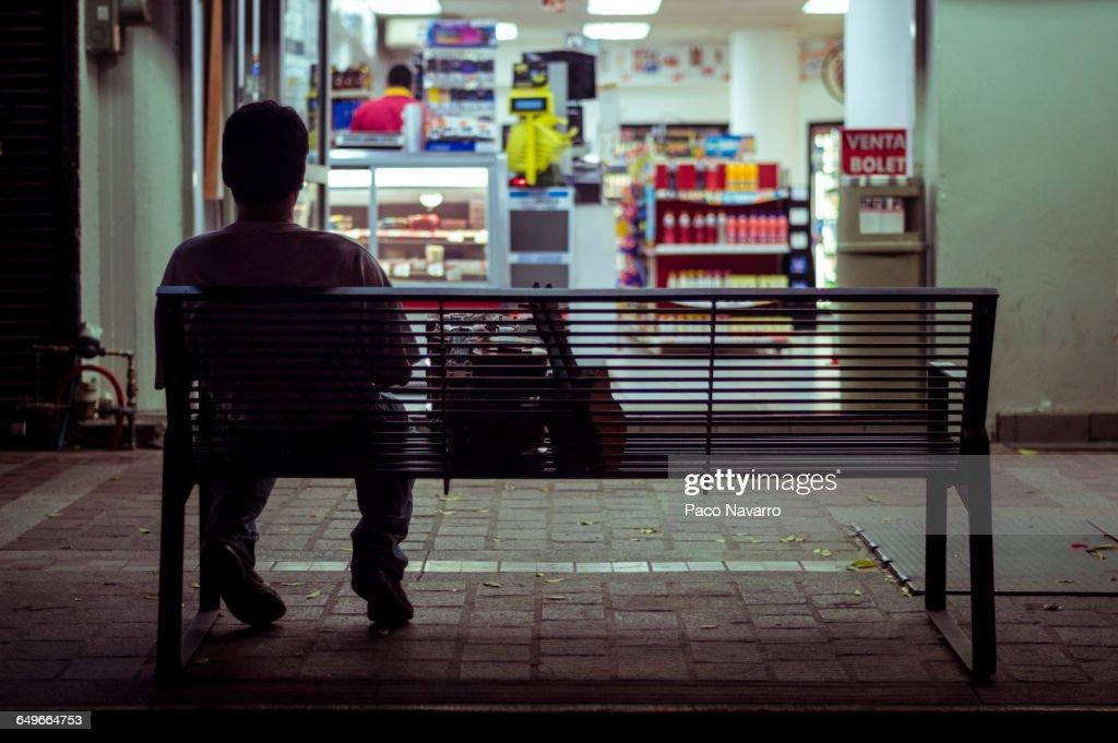 Man sitting on city bench at night : Stock Photo