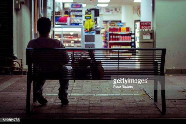 man sitting on city bench at night - convenience store stock photos and pictures