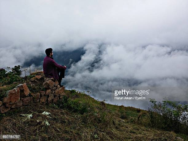 Man Sitting On Cliff Against Cloudscape