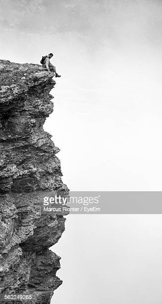 Man Sitting On Cliff During Foggy Weather