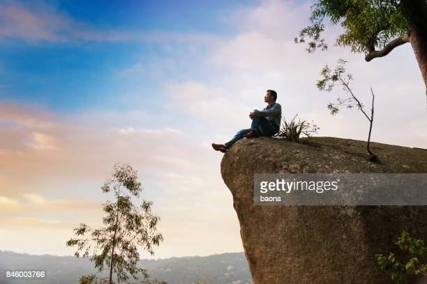 A man sitting on cliff enjoy the view