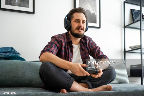 man sitting on couch and playing video game - computerspiel konsole stock-fotos und bilder
