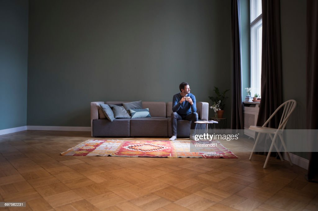 Man sitting on couch at home looking through window : Stock Photo