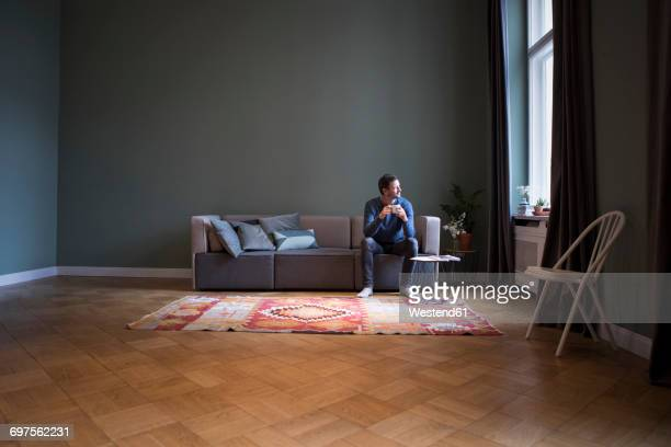 man sitting on couch at home looking through window - só um homem imagens e fotografias de stock
