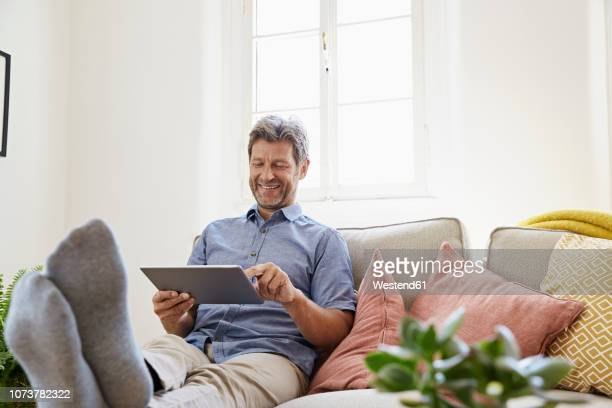 Man sitting on couch at home, using digital tablet