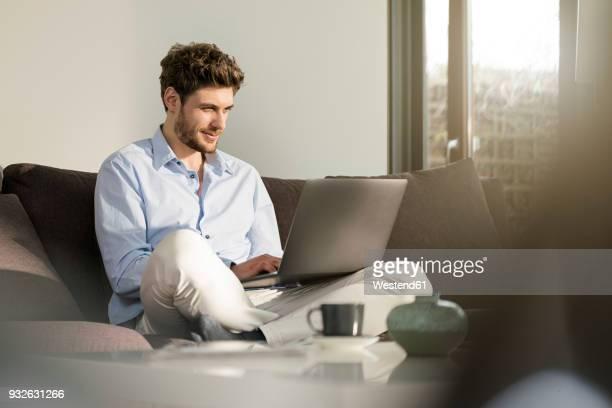 man sitting on couch at home using laptop - laptop benutzen stock-fotos und bilder