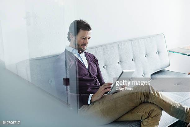 man sitting on couch holding digital tablet - only mature men stock pictures, royalty-free photos & images