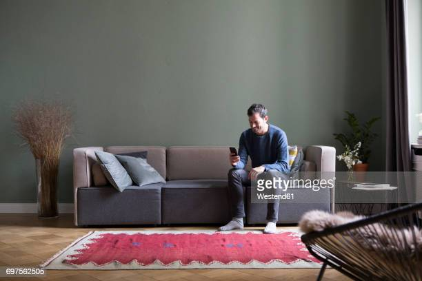 man sitting on couch in his the living room looking at smartphone - divano foto e immagini stock
