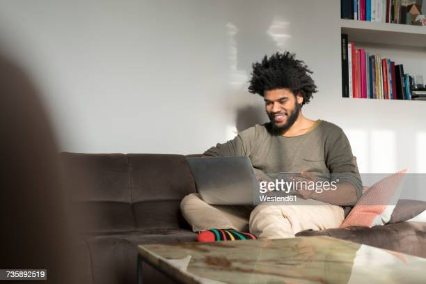 Man sitting on couch in living room with laptop and credit card