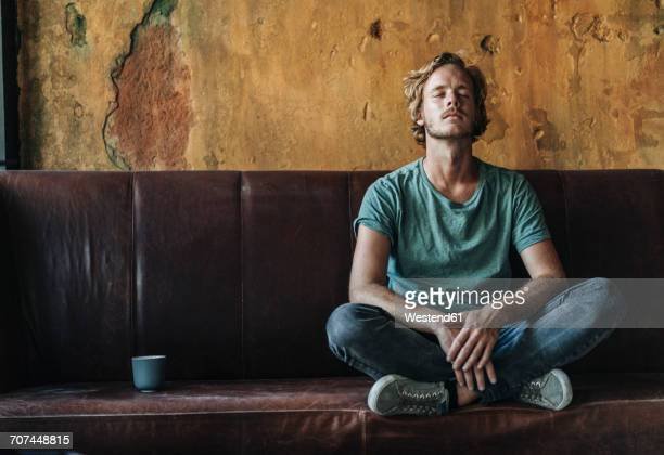 man sitting on couch in unfinished room - sitzen stock-fotos und bilder