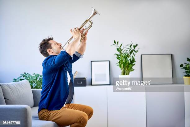 man sitting on couch playing trumpet - tromba foto e immagini stock