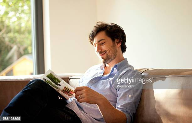 man sitting on couch reading catalogue - 雑誌 ストックフォトと画像