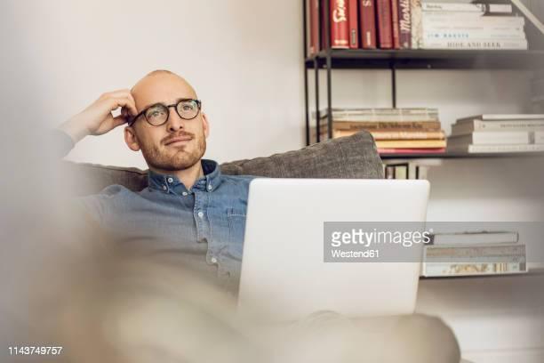 man sitting on couch, usinag laptop - solo un uomo di età media foto e immagini stock