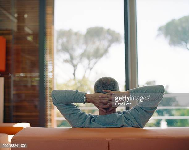 Man sitting on couch with hands behind head, rear view