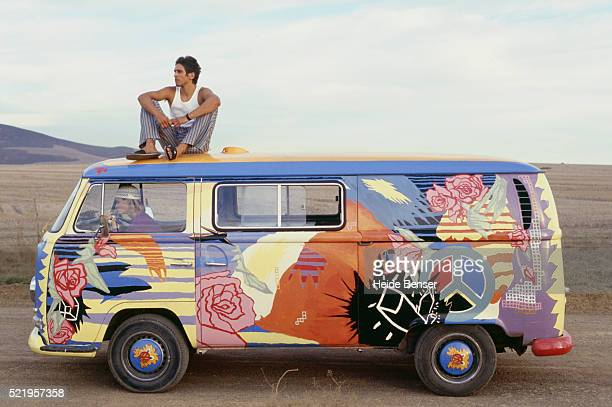 Man Sitting on Custom Painted Volkswagon Bus