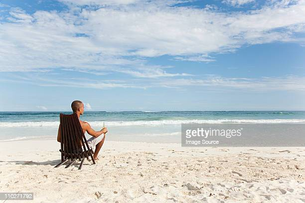 man sitting on deck chair on sandy beach - outdoor chair stock pictures, royalty-free photos & images
