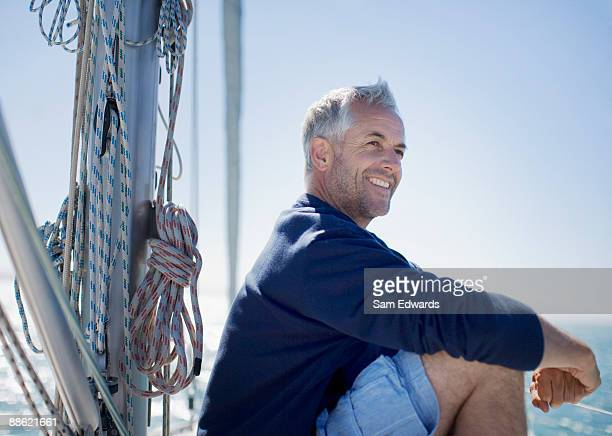 man sitting on deck of boat - sailor stock pictures, royalty-free photos & images