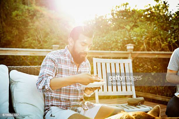 Man sitting on deck with friends eating pizza