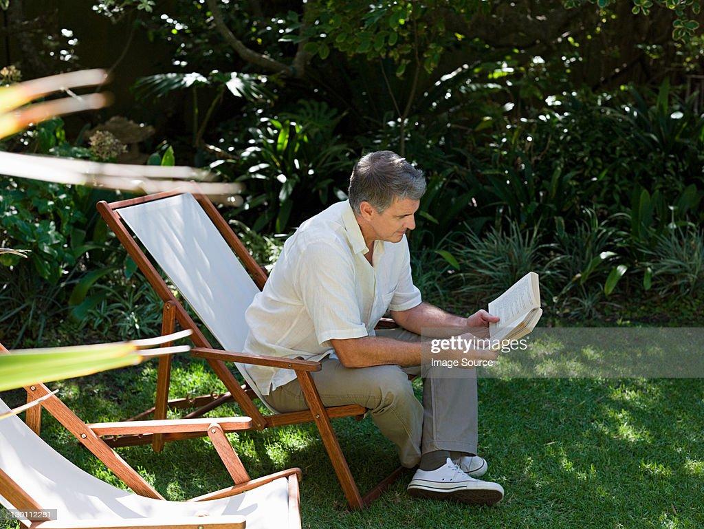 Man sitting on deckchair in garden reading book : Stock Photo